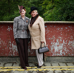 © Licensed to London News Pictures. <br /> 16/10/2016. <br /> Goathland, UK.  <br /> <br /> SUE LEONARD (L) and LORRAINE GOODWIN pose for a photograph on the bridge leading to Goathland station during the final day of the North Yorkshire Moors Railway Wartime Weekend event. <br /> The annual event brings together re-enactors and enthusiasts along the length of the NYMR heritage steam railway line to recreate the feel of the war years of the 1940's. <br /> <br /> Photo credit: Ian Forsyth/LNP