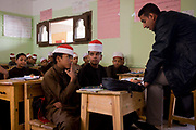 Schoolboys listen to their teacher in a classroom at the Islamic Koom al-Bourit Institute for Boys in the village of Qum (Koom), on the West Bank of Luxor, Nile Valley, Egypt. Islam in Egypt is the dominant religion in a country with around 80 million Muslims, comprising 94.7% of the population, as of 2010. Almost the entirety of Egypt's Muslims are Sunnis, with a small minority of Shia and Ahmadi Muslims. The latter, however, are not recognised by Egypt.