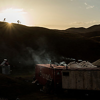 Rene Wildhaber and Tom Oehler riding to camp, Kyrgyzstan. Old shipping containers are commonly used as dwellings in rural Kyrgyzstan.