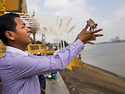 25 FEBRUARY 2015 - PHNOM PENH, CAMBODIA: A man releases birds to make merit at a Buddhist shrine in Phnom Penh.    PHOTO BY JACK KURTZ