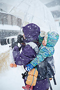 Woman with baby on her back taking photos in snow, Nozawaonsen, Japan