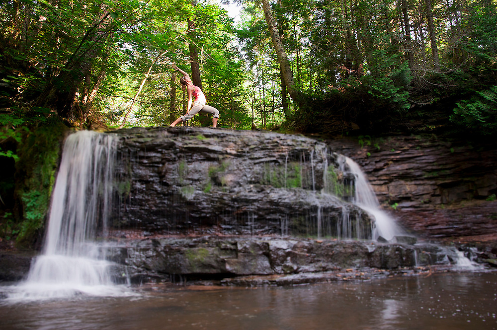 A young woman practices yoga at the head of a wilderness waterfall.