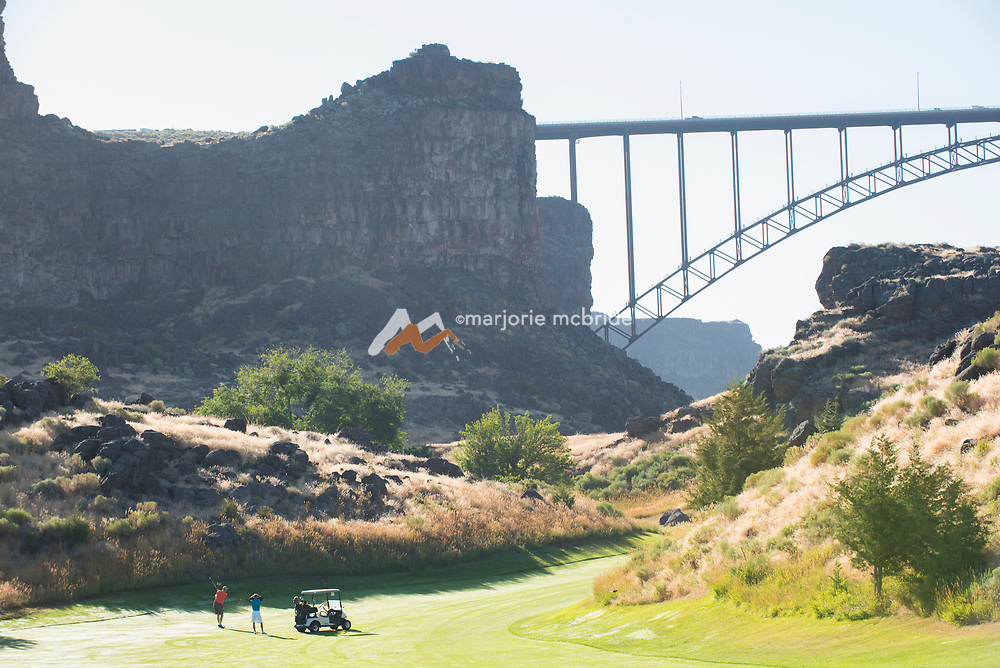 Golfers golfing on the 3rd hole at Blue Lakes Country Club, Snake River Canyon, Twith the Perrine bridge beyond. Twin Falls, Idaho.