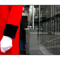 Traditional Waiter in red coat and white gloves;<br />