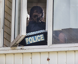 © Licensed to London News Pictures. 26/05/2018. Crawley, UK. A police officer is seen inside a block of flats in Crawley where a woman was found dead.  A man has been arrested on suspicion of murder after the woman was found in her bed. Police are appealing for witnesses to come forward.  Photo credit: Peter Macdiarmid/LNP