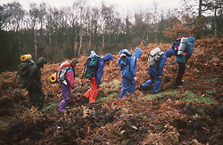 Group of secondary school pupils hiking through countryside carrying rucksacks,