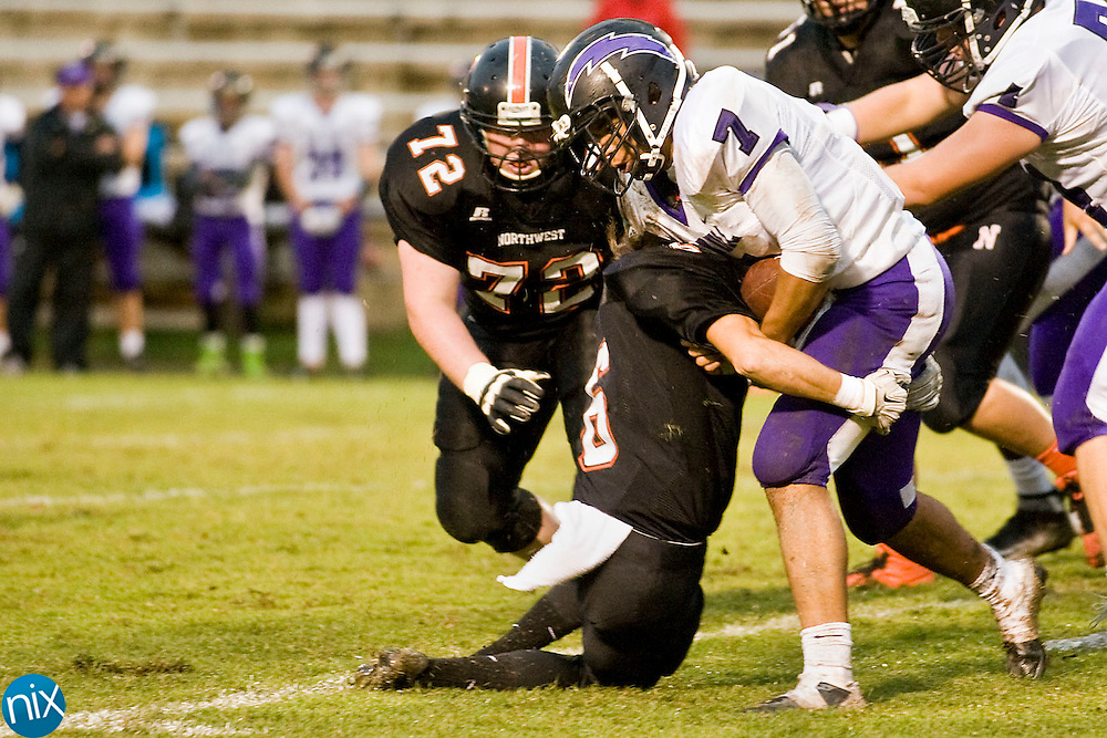 Chargers running back Tyler Arnold (7, right) is stopped by Trojans linebacker Devyn Perkins (6, left) during the Cox Mill Chargers at Northwest Cabarrus Trojans high school football game on Friday night.