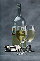 Bottle of withe wine and cups with corkscrew.