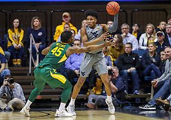 Mar 7, 2020; Morgantown, West Virginia, USA; West Virginia Mountaineers guard Miles McBride (4) passes the ball while defended by Baylor Bears guard Davion Mitchell (45) during the first half at WVU Coliseum. Mandatory Credit: Ben Queen-USA TODAY Sports