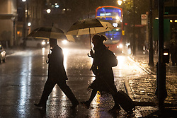 © Licensed to London News Pictures. 20/10/2021. London, UK. Members of the public shelter under umbrellas as they walk during heavy rain in Greenwich South East London. An Amber weather warning for rain is in place for parts of London and South East England.  Photo credit: George Cracknell Wright/LNP