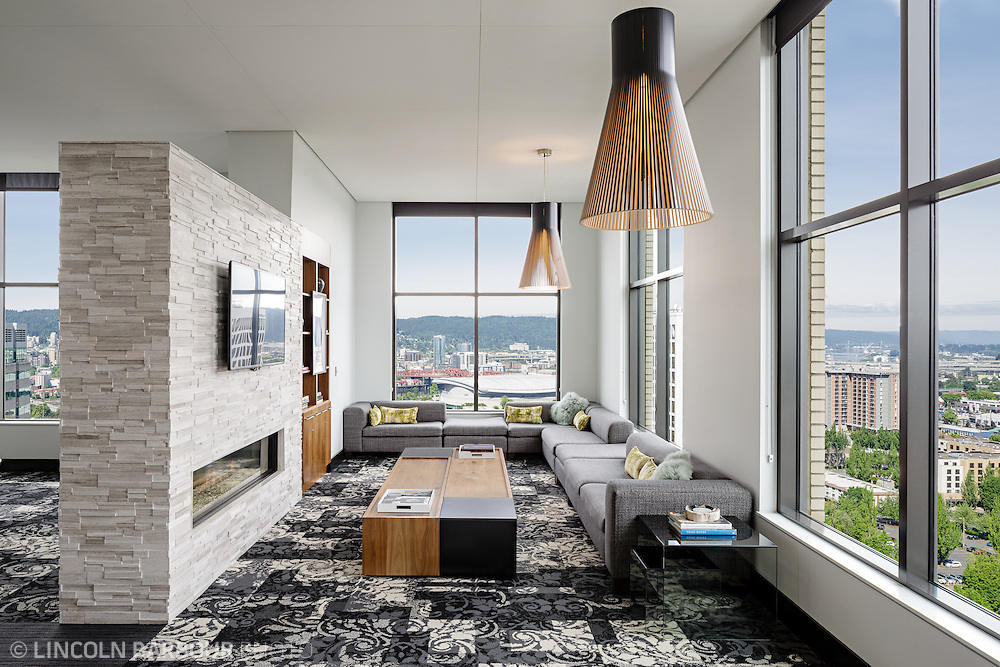A living room with modern decor and furniture in a high rise building.  Large windows give a nice view of Portland.