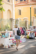 Woman walking by street market stool on summer day, Ajaccio, Corsica, France