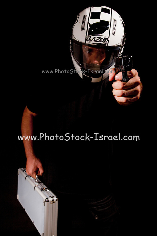 Man with motorbike helmet and money bag holds hand gun pointed at viewer - model rellease available