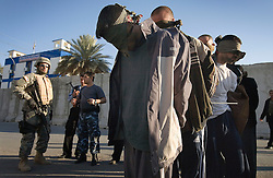 Detainees are seen in Mosul, Iraq, Dec. 13, 2005. Members of the 1st Infantry, 17th Regiment, help Iraqi forces patrol as part of an effort to provide security in preparation for Iraq's first post-Saddam parliamentary elections. The western sector is home to Mosul's primarily Sunni population, which has been resistant to the American presence in Iraq.