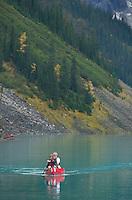 Canoeists paddling red canoes on Lake Louise, Banff National Park