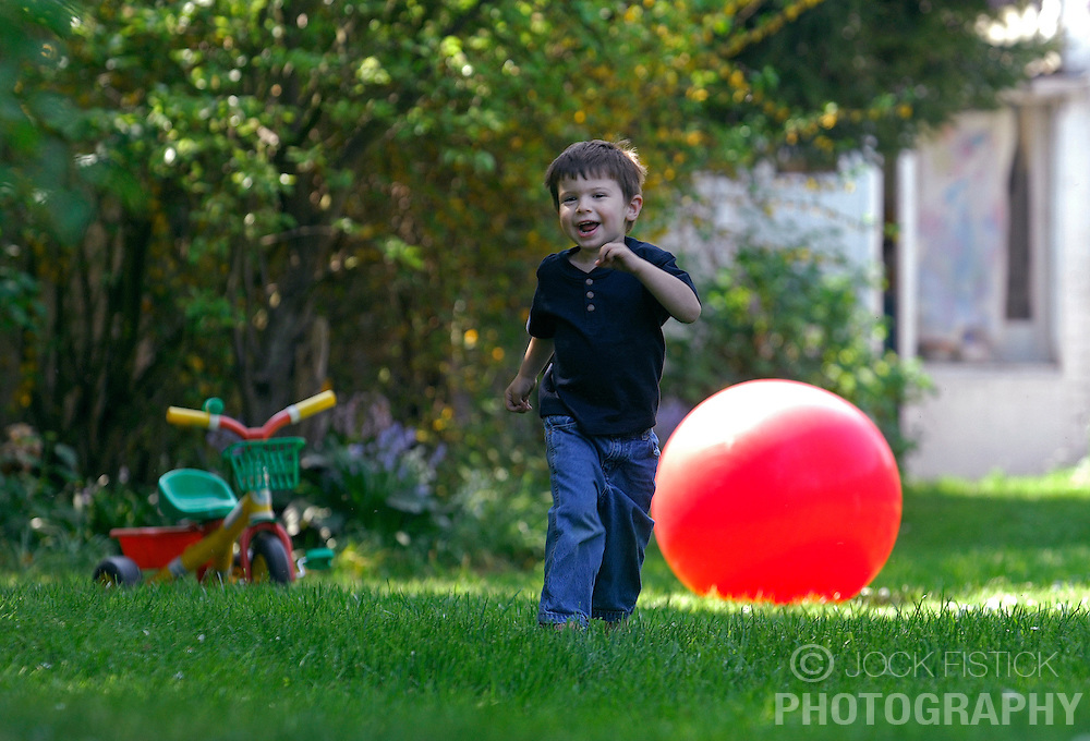 BRUSSELS, BELGIUM - APRIL-25-2007 - A happy smiling child plays with a big red ball. (PHOTO © JOCK FISTICK)