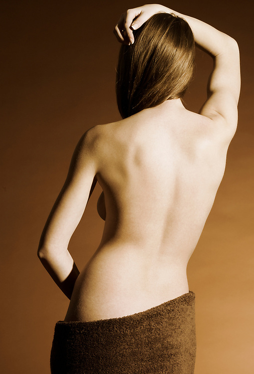 Rear view of woman's back with towel wrapped around hips