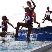 Competitors in action at the water jump in the Women's 3000m Steeplechase during the Diamond League Adidas Grand Prix at Icahn Stadium, Randall's Island, Manhattan, New York, USA. 14th June 2014. Photo Tim Clayton