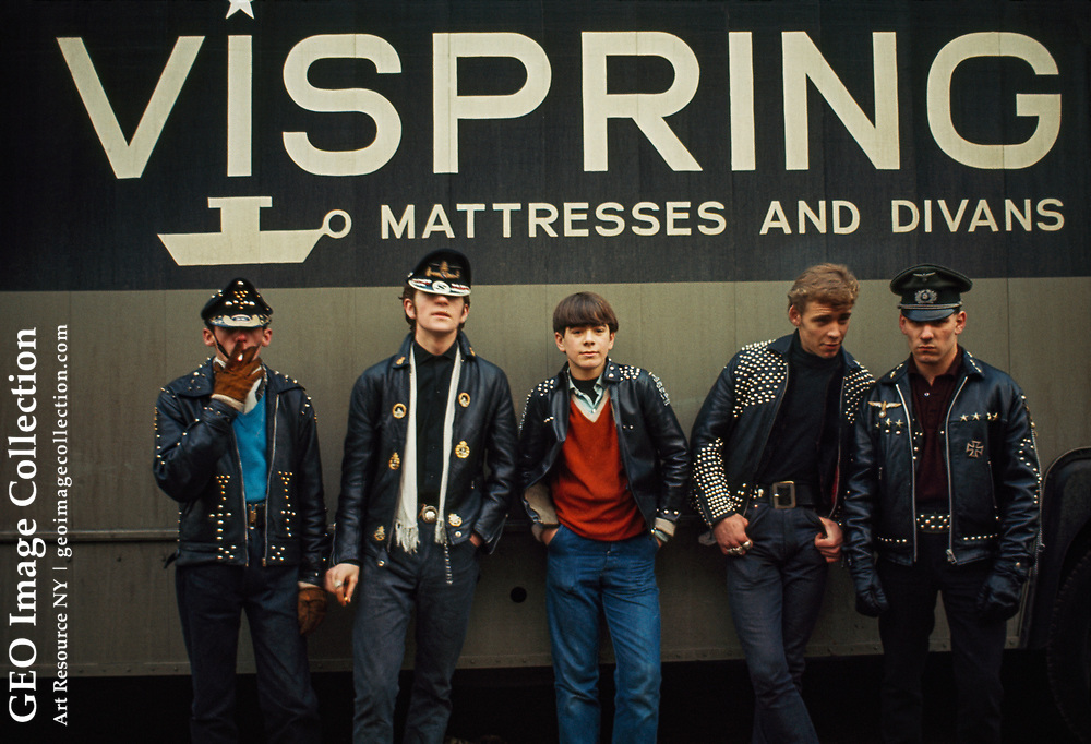 Motorcycle club members wear studded leather jackets and rakish caps.