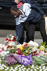 Parliament Square, Westminster, London, June 17th 2016. Following the murder of Jo Cox MP friends and members of the public lay flowers, light candles and leave notes of condolence and love in Parliament Square, opposite the House of Commons. PICTURED: A man lays a boquet of flowers among the hundreds of tributes.
