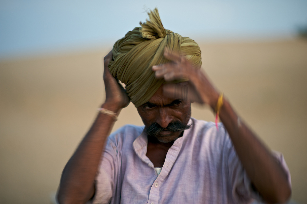 As I was preparing to take this man's portrait at dusk he paused to straighten his turban.  This was made in The Thar Desert of Rajasthan, India