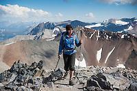 Female hiker on rocky summit of Mt. Dana (13,053 ft), Yosemite national park, California, USA