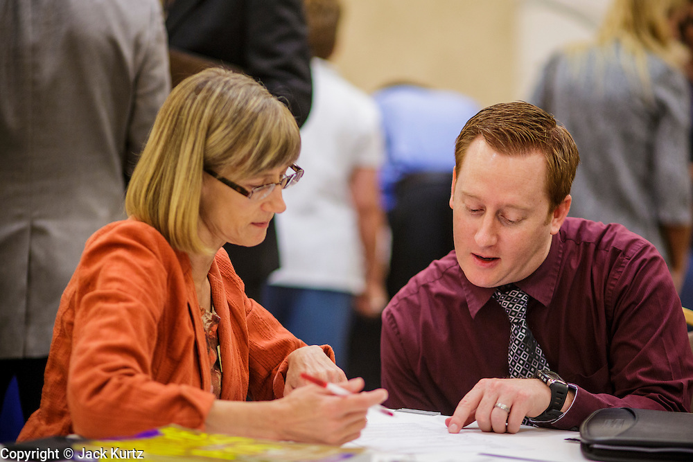 30 JULY 2012 - PHOENIX, AZ:   ERIC PERCIVAL (right) gets help with his resume from a resume coach at the Phoenix Job Fair in Phoenix, AZ. The job fair was sponsored by National Career Fairs, which organizes job fairs across the US. Several hundred people attended the job fair, with some arriving hours before it started. More than 30 employers and prospective employers were conducting interviews at the job fair. There were also resume coaches and educational institutions on site. Arizona is still grappling with the recession. The state's unemployment rate is stuck at 8.2% and the Phoenix metropolitan area has one of the highest home foreclosure rates in the United States.    PHOTO BY JACK KURTZ