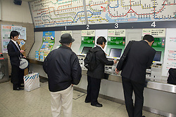 Asia, Japan, Tokyo, businessmen buying tickets for subway from vending machines