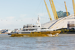 © Licensed to London News Pictures. 17/09/2019. London, UK. Gold wrapped, 175 feet long superyacht, Bellami.com arrives in London passing the Cable Car and O2 Arena on the River Thames before mooring in East India Dock. It took 13 days and 600sqm of gold chrome vinyl wrap to cover the superyacht formally known as 'Kinta' at the Port of Viareggio in Italy this year and is the largest chrome yacht wrap done fully in the water and possibly the largest chrome wrap ever. As Bellami.com arrived, it was noticed that some of the chrome wrap was already damaged and missing. Photo credit: Vickie Flores/LNP
