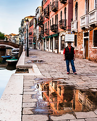 A Venetian Baker using his head to take his fresh Italian rolls to market in Venice Italy. <br /> <br /> I was taking pictures of the reflection of the buildings in the rain puddle when he came walking along.  I rapidly started trying to capture his reflection in the puddle and seeing what I was trying to do, the baker volunteered to backtrack to the puddle so I could get my image. <br /> <br /> I tried to give him some Euros for his trouble but he refused them.