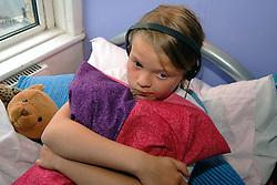 Upset girl hugging cushions
