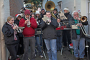 Brass band performing in street at Christmas to collect money for charity, Woodbridge, Suffolk, England