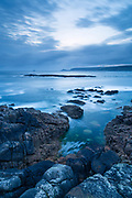 A rocky dusk scene at Sennen Cove looking across the bay towards Cape Cornwall. Cornwall, England, UK.