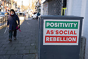 On the last day of the year, people pass a paste up piece of slogan based street art which reads Positivity as Social Rebellion on Kings Heath High Street as people brace themselves for further months of coronavirus restrictions on 31st December 2020 in Birmingham, United Kingdom. Small businesses have struggled through the Covid-19 pandemic and many have closed down altogether, as the recession in the economy deepens as the crisis continues.