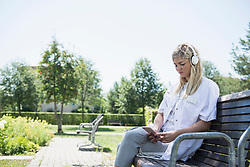 Female doctor listening to music with smart phone and headphones at garden, Bavaria, Germany, Europe