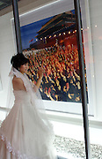 A woman in a wedding dress poses next to a photograph of a scene from the cultural revolution. China's art scene is becoming popular among foreign art collectors pushing prices higher.