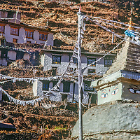 Traditional houses rise behind a Tibetan Buddhist stupa and prayer flags in Namche Bazar, leading town of the Sherpas in the Khumbu region of Nepal's Himalaya. Photo from 1979. These house have all been replaced by more modern ones.