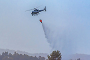 A police helicopter is used during a fire drill to airlift water to the fire zone The water is dropped in the required area