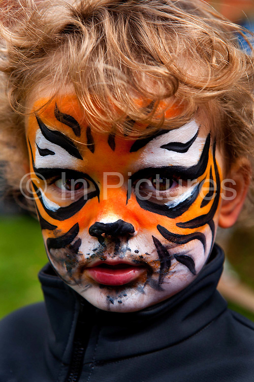 Child with tiger face pain in the Thames Festival, an autumn weekend celebration each September on the banks of the river Thames. The House of Fairy Tales presents their spectacular, participative Travelling Art Circus! Come and take part in a series of magical water-themed workshops and activities for families and people of all ages.<br /> With the help of over 100 primary schools from 33 London boroughs, six interactive themed exhibition spaces have been created by the children and artists who took part in the Thames Festival's pan-London education project, with a fully functioning waterwheel sculpture at its centre.