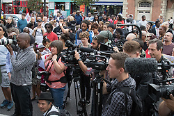 Tottenham, London, August 4th 2015. Family, friends and supporters of alleged gangster Mark Duggan, who was shot and killed by police on 4th August 2011 in Tottenham, commemorate his death which led to widespread uprisings and riots, by marching from Broadwater Farm estate to Tottenham police station. His family is demanding a public inquiry into the role of Operation Trident, set up to fight gun and knife crime amongst the black community, whose officers they accuse of putting guns out on the streets of London. PICTURED: Part of the crowd gathered outside Tottenham Police Station.  // Contact: paul@pauldaveycreative.co.uk Mobile 07966 016 296