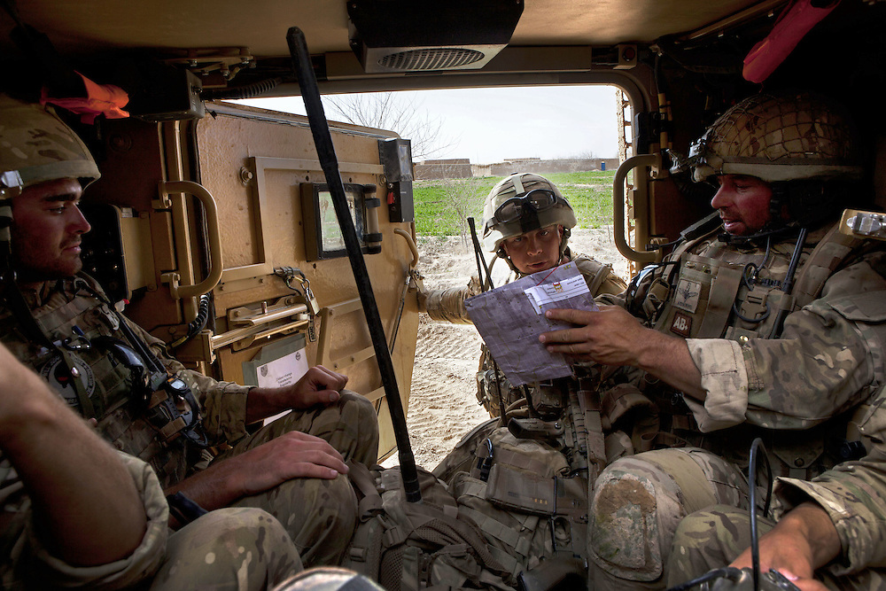 British soldiers of 16 Air Assault Bde's elite BRF (Brigade Reconnaissance Force) examine a map as they move from compound to compound searching for weapons and explosives as part of an operation in the village of Kakaran in Helmand Province, Southern Afghanistan on the 14th of March 2011.