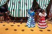Two young spanish girls play outside a family Caseta during the Spring Feria in Seville, Spain. Both dressed in traditional flamenco dresses, the two friends stand in bright sunshine as a younger boy peers out from the canopy screen that keeps the marquee interior cool. <br /> It is a lively event that Seville holds annually in the vast fairground area on the far bank of the Guadalquivir River. Rows of temporary marquee tents, or casetas, host families, corporations and friends into the late hours during the April Fair which begins begins two weeks after the Semana Santa, or Easter Holy Week in the Andalusian capital.