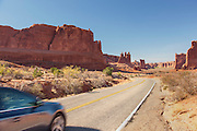 Car on a road going through Arches National Park, Utah, United States of America