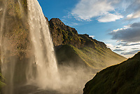 The 60 meter tall Seljalandsfoss tumbles over a cliff in the evening sunlight.