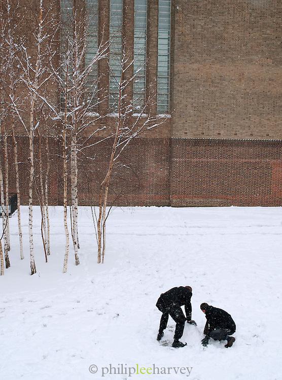 People making a snowman outside the Tate Modern art gallery in London, UK