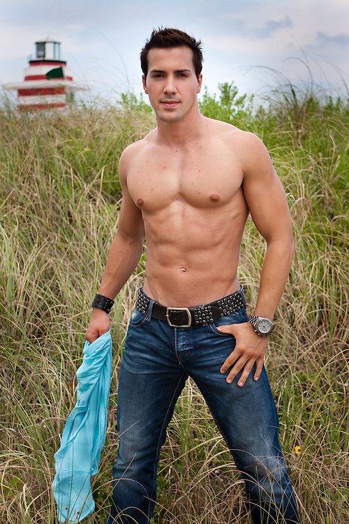 Muscular man poses in front of Beach station in South Beach, Florida
