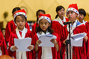 24 DECEMBER 2013 - BANGKOK, THAILAND: The children choir sings carols during Christmas services at Holy Redeemer Church in Bangkok. Thailand is predominantly Buddhist but Christmas is widely celebrated throughout the country. Buddhists mark the day with secular gift giving but there are about 300,000 Catholics in Thailand who celebrate religious Christmas. Catholics first came to Thailand (then Siam) in 1567 as chaplain for Portuguese mercenaries in the employ of the Siamese monarchy. There has been a continuous Catholic presence in Thailand since then.   PHOTO BY JACK KURTZ