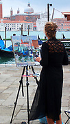 Young Female Street Painter. A young woman paints scene of gondolas and the church of San Giorgio Maggiore.