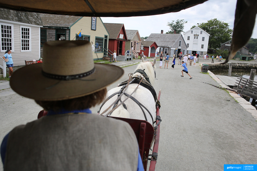 A horse and carriage passes the historic waterfront at Mystic seaport. Mystic, Connecticut. 21st July 2013. Photo Tim Clayton
