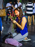 18 FEBRUARY 2016 - BANGKOK, THAILAND: A woman prays, holding nine red roses and sticks of incense, at the Trimurti Shrine in Bangkok. Every Thursday night, starting just after sunset and peaking at 21.30, hundreds of Bangkok single people, or couples seeking guidance and validation, come to the Trimurti Shrine at the northeast corner of Central World, a large Bangkok shopping mall, to pray to Lord Trimurti, who represents the trinity of Hindu gods - Brahma, Vishnu and Shiva. Worshippers normally bring an offering of red flowers, fruits, one red candle and nine incense sticks. It's believed that Lord Trimurti descends from the heavens at 21.30 on Thursday to listen to people's prayers. Although most Thais are Buddhists, several Hindu traditions have been incorporated into modern Thai Buddhism, including reverance for Trimurti.       PHOTO BY JACK KURTZ